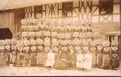 Ansichtskarte AK Trachtenverein viele Frauen mit imposantem Kopfschmuck vor Fachwerkhaus